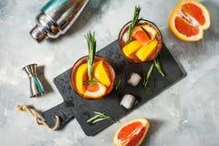 A toranja e os alecrins descaroçam o cocktail, refrescando a bebida com gelo fotos de stock royalty free