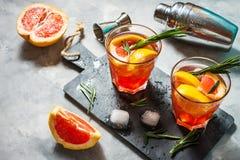 A toranja e os alecrins descaroçam o cocktail, refrescando a bebida com gelo foto de stock
