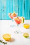 A toranja e os alecrins descaroçam o cocktail, refrescando a bebida com gelo imagem de stock