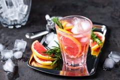 A toranja e os alecrins frescos descaroçam o cocktail com suco, bebida de refrescamento ou bebida do citrino frio do verão com ge Fotos de Stock Royalty Free