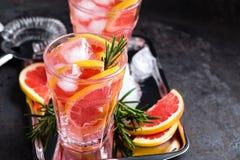 A toranja e os alecrins frescos descaroçam o cocktail com suco, bebida de refrescamento ou bebida do citrino frio do verão com ge Imagens de Stock Royalty Free