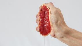 A toranja, mão espreme para fora o close up do suco video estoque