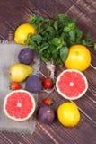 Toranjas, peras, limões, figos, morango, pomelo, hortelã no fundo de madeira; ainda vida com frutos Foto de Stock Royalty Free