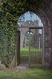 Torbogen mit hölzernen Toren an der alten Abtei in Brecon erleuchtet in Wales Stockfotos