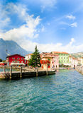Torbole, Italy - September 21, 2014: Lake Garda boardwalk with houses, tourists and boats Royalty Free Stock Image