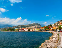 Torbole, Italy - September 21, 2014: Lake Garda boardwalk with houses, tourists and boats Stock Images