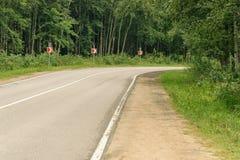 Torcendo a estrada entre as árvores Fotos de Stock Royalty Free