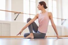 Torcer el cuerpo en la clase de la yoga imagenes de archivo