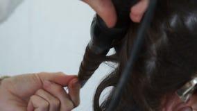 Torcer un filamento del pelo en un hierro que se encrespa metrajes