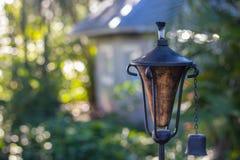 Torch в саде с расплывчатой предпосылкой дома стоковое фото