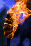 Torch. Closeup of nice burning torch against dark blue night sky background stock photo
