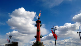 The torch with fire on the Rostral column in St. Petersburg during the celebration of Victory Day. Beautiful cloudy sky Stock Images