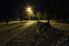 A torch-light inundates a nightly snow bound road on the outskir Royalty Free Stock Photos