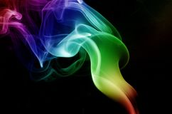 Torch Smoke. Circular rainbow colored smoke rising from burning incense like a torch royalty free stock photos