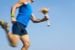 Torchbearer-Athlet Running mit Sport-Fackel-blauem Himmel stockfoto