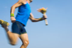 Torchbearer Athlete Running with Sport Torch Blue Sky Stock Photo