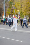 Torchbearer carries the Olympic flame Stock Photos