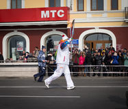 Torchbearer carries the Olympic flame. Stock Image