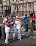 Torchbearer carries the Olympic flame. Royalty Free Stock Photos