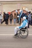 Torchbearer in einem Rollstuhl, der eine Fackel auf dem Paralympic T trägt Lizenzfreie Stockfotografie