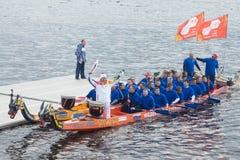 Torchbearer Ignat Kovalev auf einem Boot mit Drachen gehen voran Lizenzfreie Stockbilder