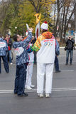 torchbearer passes the Olympic flame Royalty Free Stock Photos