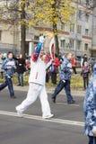 Torchbearer trägt die olympische Flamme Lizenzfreie Stockbilder