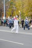 Torchbearer trägt die olympische Flamme Stockfotos