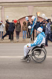Torchbearer in a wheelchair carrying a torch on the Paralympic T Royalty Free Stock Photography