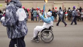 Torchbearer in a wheelchair carrying a torch on the Paralympic Torch Relay