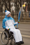 Torchbearer in a wheelchair with a torch Royalty Free Stock Photo