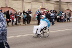Torchbearer in a wheelchair with a torch Stock Photo