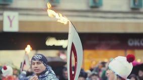 Torche olympique de Sotchi de course de relais dans le St Petersbourg Début femelle de porteur de flambeau couru avec la flamme S banque de vidéos
