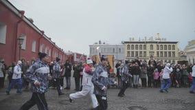 Torche olympique de Sotchi de course de relais dans le St Petersbourg, le Peter et le Paul Fortress Porteur de flambeau avec la f banque de vidéos