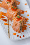 Torched Salmon Maki Sushi with Shrimp Tempura, Avocado and Cheese inside. Topping with Sauce, Ebiko Shrimp Egg and Scallion Royalty Free Stock Photos