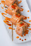 Torched Salmon Maki Sushi with Shrimp Tempura, Avocado and Cheese inside. Topping with Sauce, Ebiko Shrimp Egg and Scallion Royalty Free Stock Image