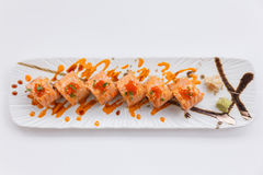 Torched Salmon Maki Sushi with Shrimp Tempura, Avocado and Cheese inside. Topping with Sauce, Ebiko Shrimp Egg and Scallion Stock Photo