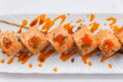 Torched Salmon Maki Sushi with Shrimp Tempura, Avocado and Cheese inside. Topping with Sauce, Ebiko Shrimp Egg and Scallion Stock Images