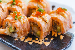 Torched Salmon Roll with Prawn Tempura Inside.Topping with Cheese, Ebiko Prawn Eggs, Scallion and White Sesame.  Royalty Free Stock Photography