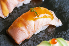 Torched Salmon Sushi with Sauce Served on Black Stone Plate. Royalty Free Stock Photos