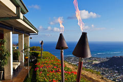 Torches and million dollar ocean view. Lit torches in the early evening at the edge of a luxurious home with a magnificent ocean view from a Honolulu hilltop Stock Image