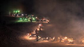 Torchlight descent down ski slope by ski instructors and mountain rescue services to celebrate new year.