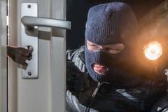 Torcia elettrica mascherata della tenuta dello scassinatore mentre provando a rompere finestra l fotografie stock libere da diritti
