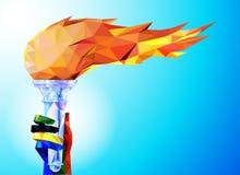 Torcia, fiamma Una mano dai nastri olimpici tiene la tazza con una torcia su un fondo blu in un triangolo geometrico XXIII del po Fotografie Stock