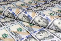 Torcido en un tubo billetes de banco de cientos dólares en el fondo de cientos billetes de dólar Imagen de archivo libre de regalías