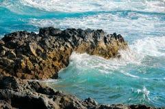 Torcoiuse waves break on black lava rocks Royalty Free Stock Photo