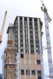 Toren de bouwkraan tegen de blauwe hemel De gebouwen in aanbouw zijn zichtbaar Royalty-vrije Stock Foto