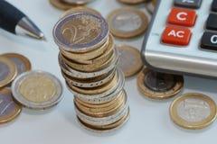 Toren van Euro muntstukken met pen en calculator Stock Foto's