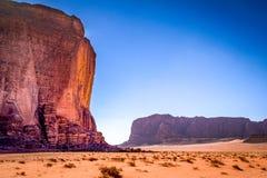 Torenhoge klippen van rode, rotsachtige dagzomende aardlagen onder het enorme oranje woestijnzand van Wadi Rum royalty-vrije stock foto