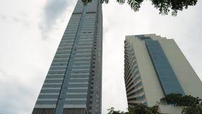 Torenhoog skyscriper en de bureaubouw met bomen en installaties op het balkon stock video